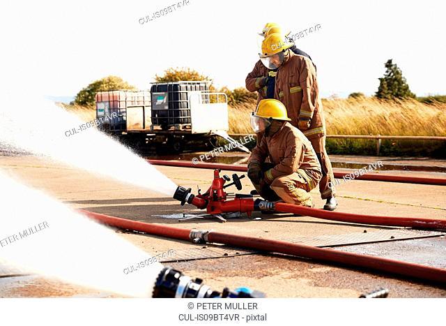 Firemen training to use fire hose, Darlington, UK