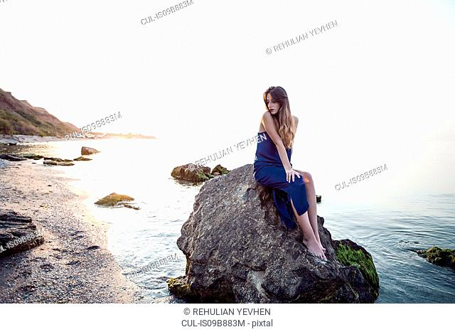 Young woman sitting on beach rock, Odessa, Ukraine
