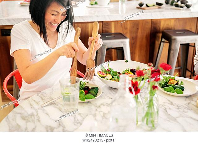 A woman using salad servers to load her plate with fresh salad leaves