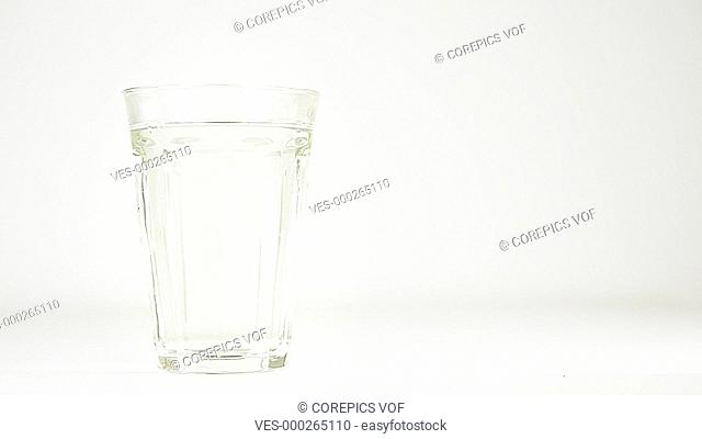 Multi vitamin effervescent tablet being dropped into a glass of water and dissolving against a white background