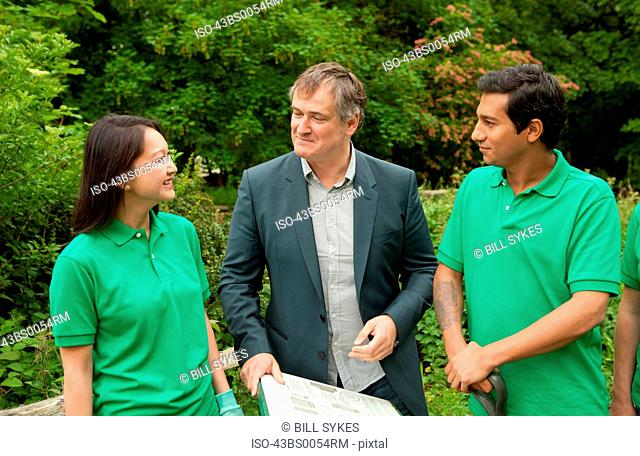 Gardeners with businessman in park