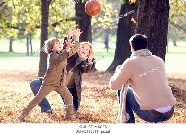 Family playing with ball in autumn forest