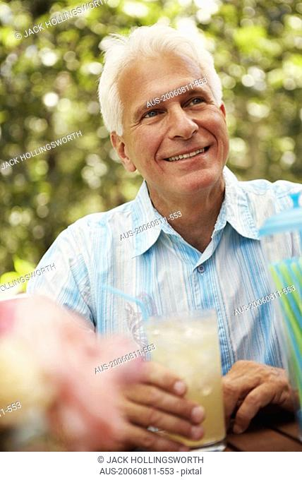 Close-up of a mature man holding a glass of a juice and smiling
