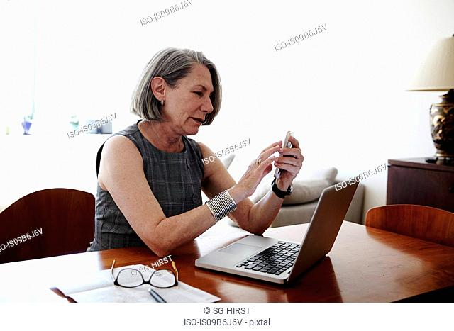 Senior businesswoman sitting at desk, laptop in front of her, using smartphone
