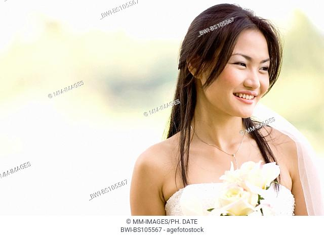 A beautiful young asian woman in a wedding dress holding two cream-coloured roses