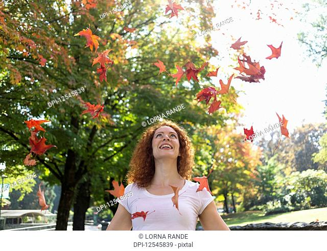 Portrait of a woman with red, curly hair throwing autumn coloured leaves in the air; Burnaby, British Columbia, Canada