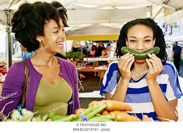 Women smiling together at outdoor market