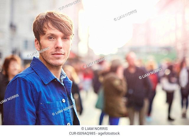 Portrait of mid adult man on crowded street, London, UK