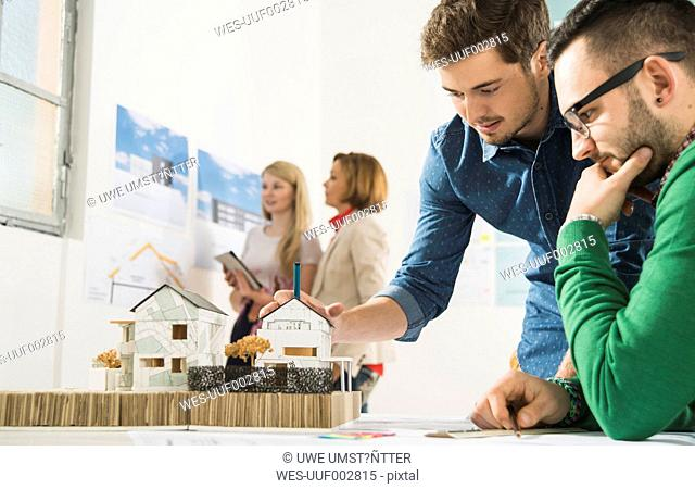 Young architects in office looking at architectural model