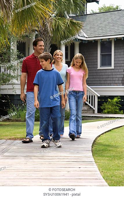 Caucasian family of four walking down suburban sidewalk with house in background