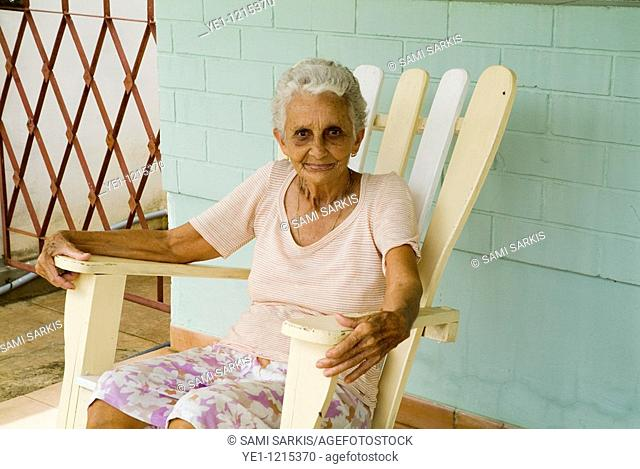 Portrait of a senior Cuban woman sitting on an adirondack chair on her porch, Vinales, Pinar del Rio Province, Cuba