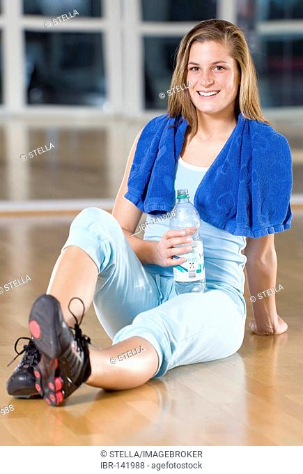 A young woman with a water bottle and a towel after her workout