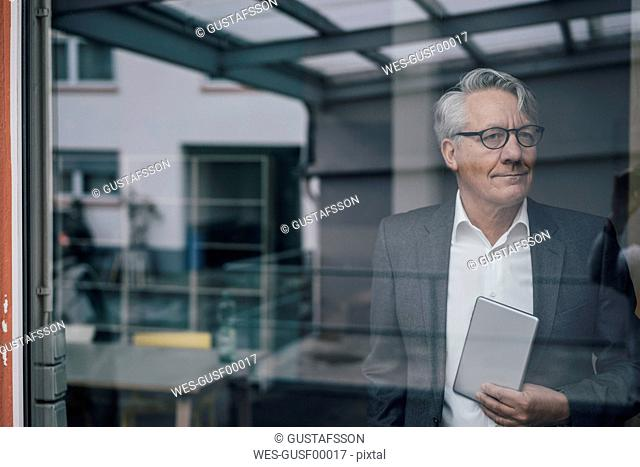 Confident senior businessman behind windowpane