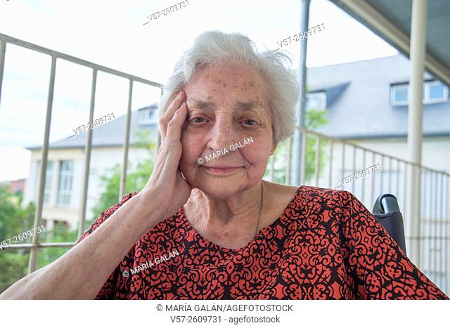 Portrait of elderly woman in a nursing home, smiling and looking at the camera. Close view
