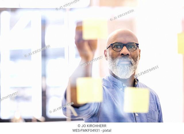 Portrait of businessman taking adhesive note from glass wall in office