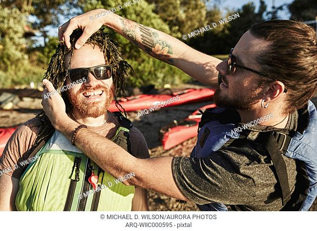 Photograph of two friends having fun with seaweed, Portland, Maine, USA