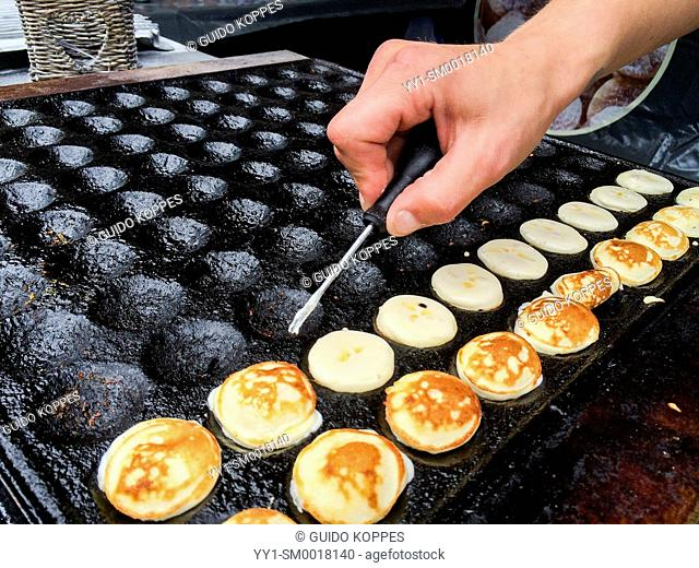 Tilburg, Netherlands. Making Dutch Mini Pancakes of Poffertjes at the weekly Saturday market