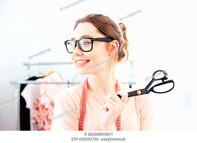 young woman seamstress smiling and holding scissors in design studio