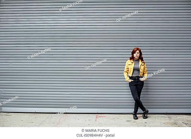 Portrait of young woman with red hair, in urban environment