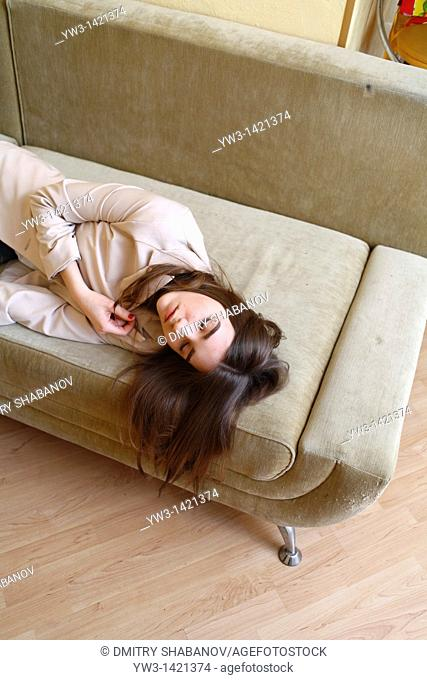 Young woman in jeans sleeping on sofa