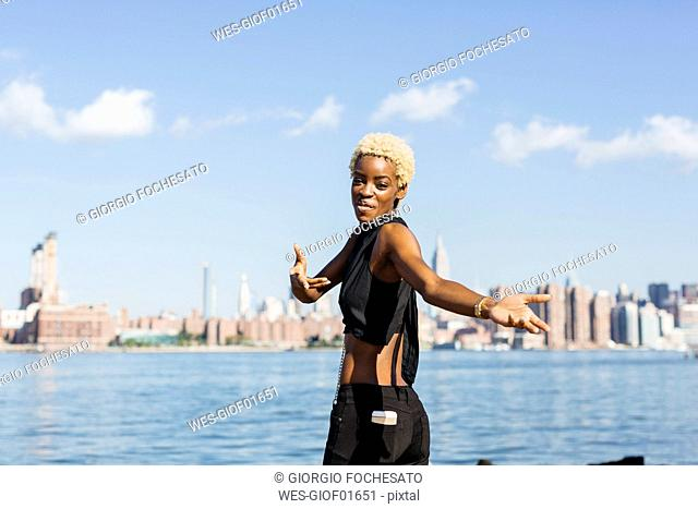 USA, New York City, Brooklyn, smiling young woman at East River