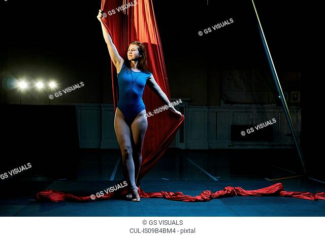 Young female aerial acrobat poised holding red silk rope