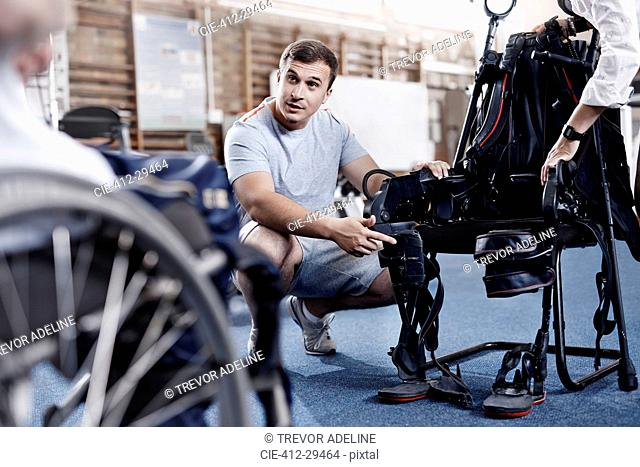 Physical therapist explaining equipment to man in wheelchair