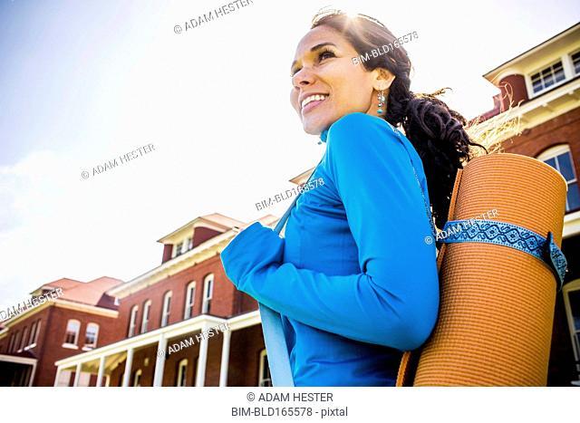 Hispanic woman carrying yoga mat outdoors