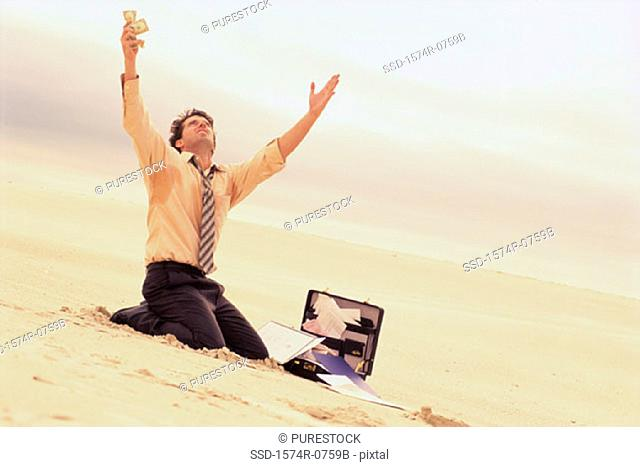 Businessman kneeling on the beach with his arms raised