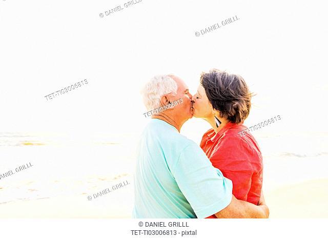 Older couple kissing on beach at sunrise