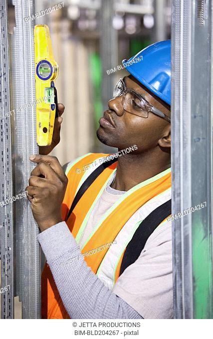 African American worker adjusting switchboards