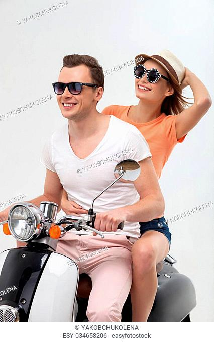 It is great to travel with you. Portrait of cute loving couple sitting on scooter. They are looking forward and laughing. Isolated