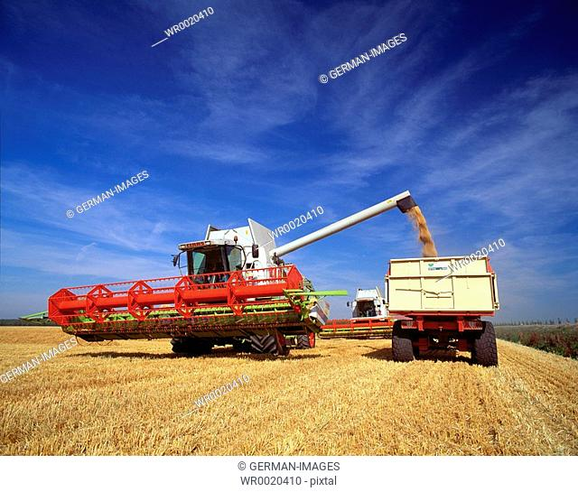 Combine and tractor harvesting crop