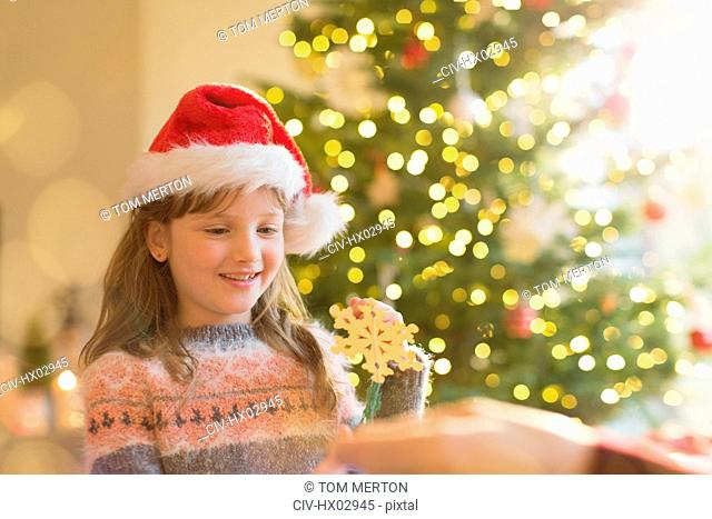 Girl in Santa hat holding snowflake ornament in front of Christmas tree