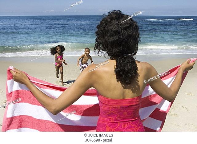 Boy and girl 5-7 running from sea towards mother on sandy beach, woman holding striped towel, rear view