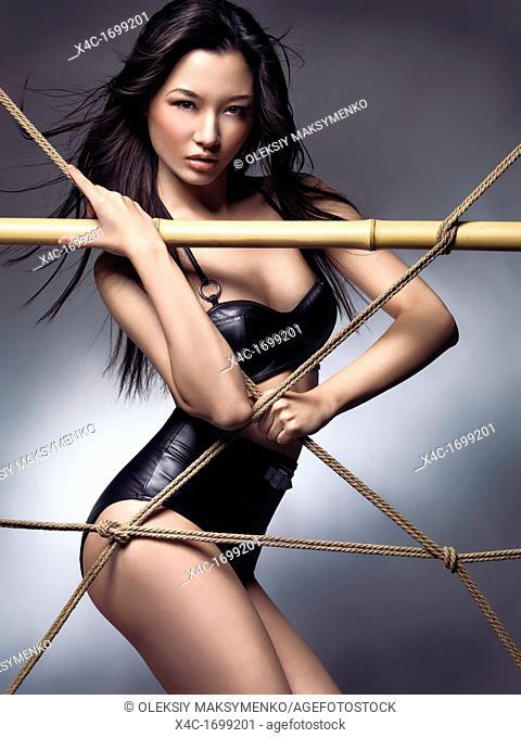 Edgy fashion photo of a beautiful sexy asian woman wearing a stylish black bikini swimsuit