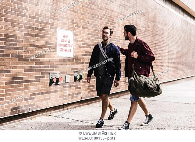 Two friends with bags walking on pavement
