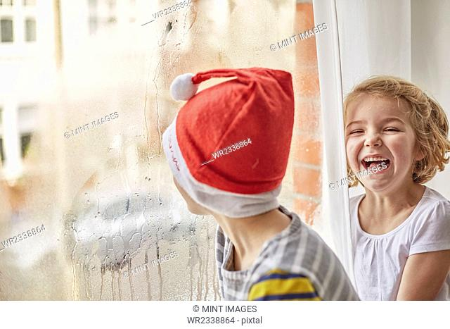 Christmas morning in a family home. A boy in a Santa hat looking out of a bedroom window and his sister laughing beside him