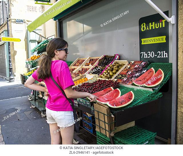 Young teen, preteen smiling and looking at the outdoor window front store of a local french grocery store