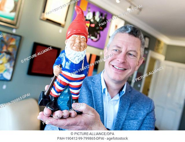 12 April 2019, Hamburg: Michael Kerle, Managing Director of the auction house Stahl, holds a garden gnome painted by former Chancellor Helmut Schmidt (SPD)