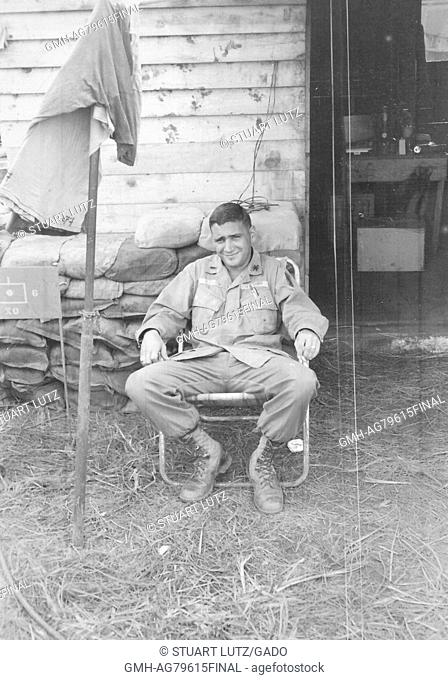 A United States Army serviceman relaxing in a lawn chair, he is smoking a cigarette near the entrance to a wooden building where equipment is visible spread out...