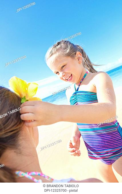 A young girl putting a tropical flower into her mother's hair on the beach; Hawaii, United States of America