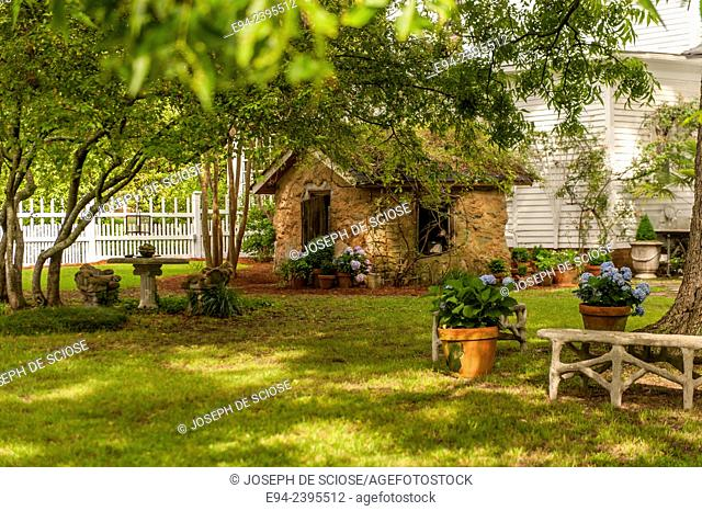 A garden shed with hydrangeas and boxwoods in terra cotta pots.Georgia USA