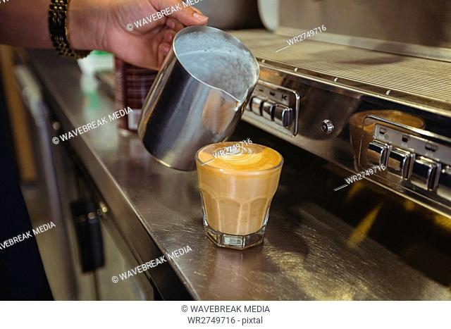 Waitress pouring milk into coffee cup at counter