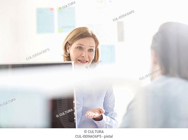 Businesswoman explaining to male colleague in office