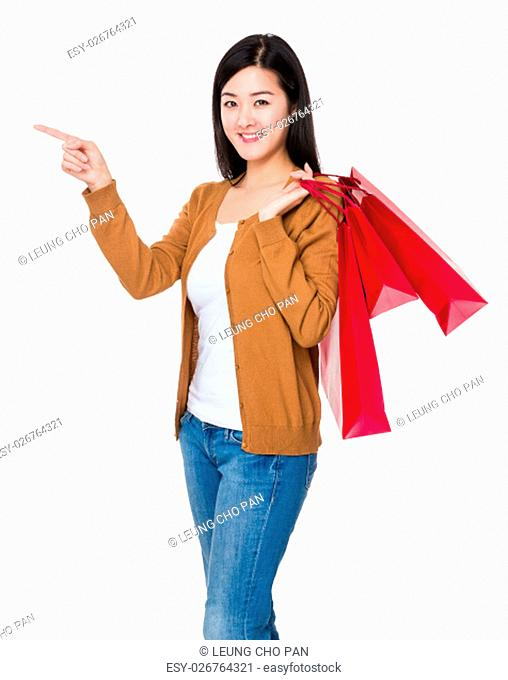 Asian young woman hold with shopping bag and finger point up