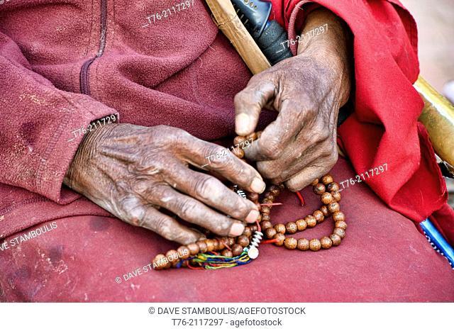 Tibetan pilgrim and prayer beads at the Boudhanath Stupa in Kathmandu, Nepal