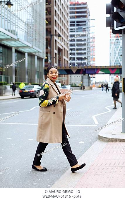 UK, London, fashionable businesswoman crossing the street