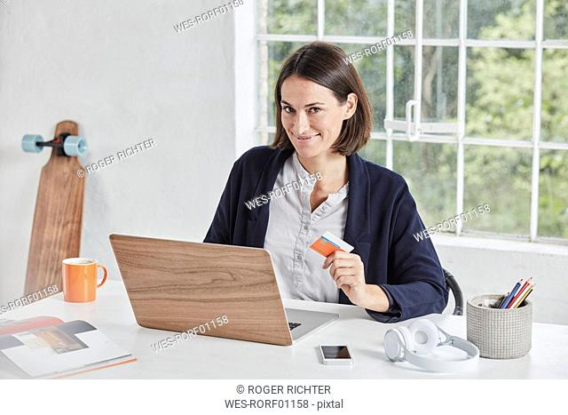 Portrait of smiling businesswoman with laptop on desk holding card