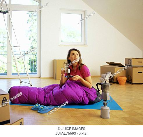 View of a young woman camping in her unfinished living room